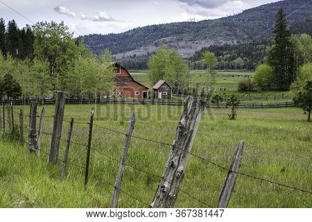 Red Barn In Rural North Idaho. An Old Fence Leads Toward A Red Barn In North Idaho.