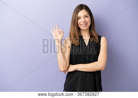Portrait Of A Woman In Her 40s Making An Okay Sign With Her Hand In A Studio And Smiling