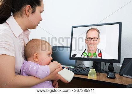 Woman With Kid In Online Video Conference Call With Doctor
