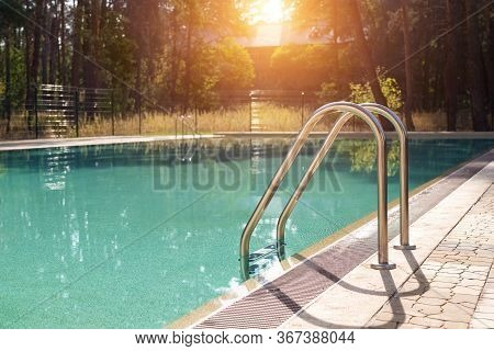 Big Luxury Empty Rectangular Swimming Pool With Clean Blue Water And Ladder At Tropical Forest Beach