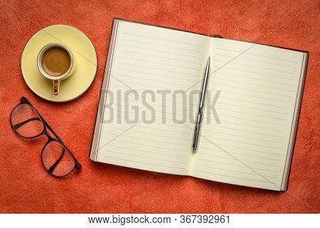blank opened  notebook or journal with a cup of coffee and reading glasses, journaling concept