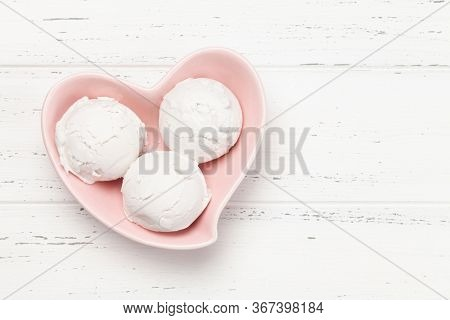 Vanilla ice cream scoops in heart shaped bowl on wooden background. Top view with copy space. Flat lay