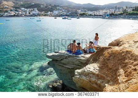 Agia Pelagia, Crete, Greece - 24 July 2014: Girls Chatting On A Rock Along The Turquoise Ocean On A