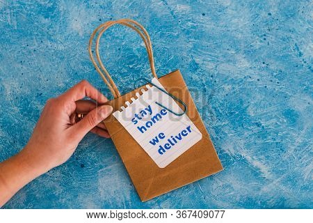 Hand Holding Takeaway Shopping Bags With Stay Home We Deliver Message.