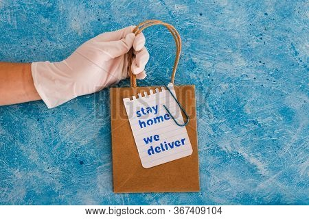 Hand With Glove Holding Takeaway Shopping Bags With Stay Home We Deliver Message.