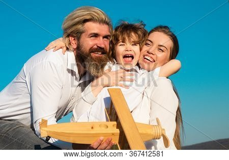 Happy Family Hug Embrace Outdoors. Cheerful Family Having Fun Outdoors. Child Playing With Mother An