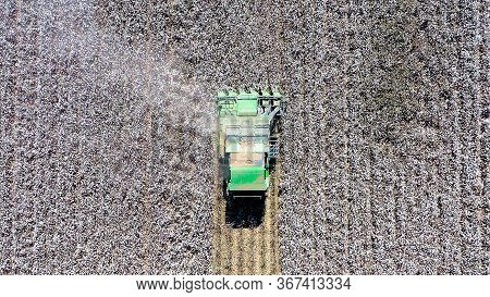 Aerial Image Of A Large Cotton Picker Harvesting A Field.