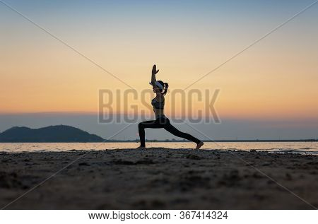 Woman Practicing Yoga During Surrealistic Sunset At The Seaside. Healthy Concept And Workout.