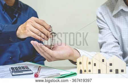 Real Estate Agent Giving House Key To Customer. Client Signing Mortgage Loan Contract Agreement. Buy