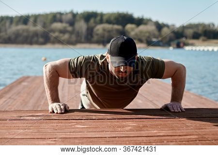 An Adult Athletic Man Performs Push-ups On A Pier On The Lake. A Man Is Engaged In Outdoor Sports. S