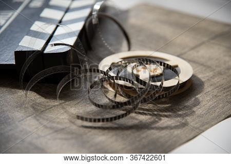 Roll Of Film With Movie Camera And Movie Clapper On Light, Illuminated Table. Filming Accessories