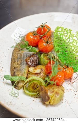 Fried walleye fillet with potatoes, leek, cherry tomatoes and mushrooms on plate