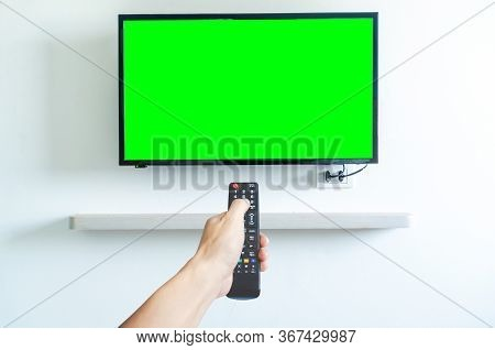 Hand Holding Tv Remote Controller Over Green Screen A Modern Television Set. Place For Your Advertis