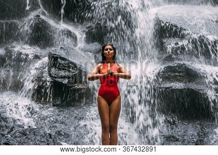 A Woman Does Yoga At A Waterfall. Healthy Lifestyle. The Concentration Of The Body. A Woman Does Yog