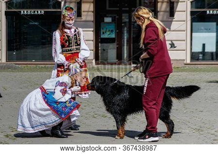 Uzhgorod, Ukraine - May 21, 2020. A Girl In A Ukrainian National Costume Kisses A Dog During An Art