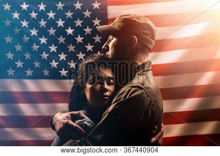 Veterans Day, Memorial Day. A Soldier Embraces His Woman. Couple On The Background Of The American F