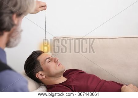 Psychotherapist Using Pendulum During Hypnotherapy   Session In Office