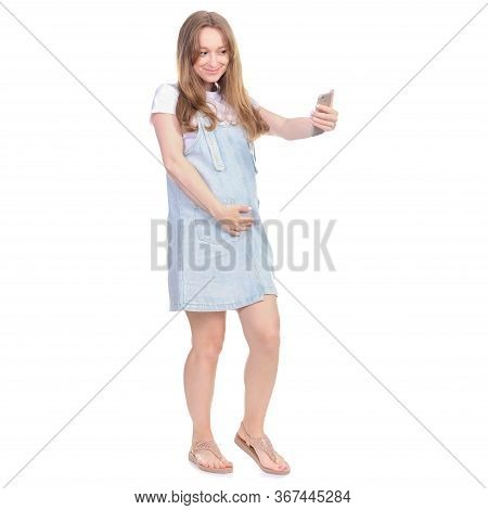 Pregnant Woman In Denim Sundress Standing Looking Smiling, Making Selfie On Smart Phone On White Bac