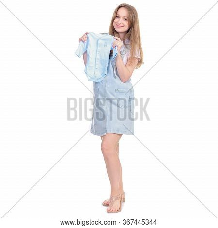 Pregnant Woman In Denim Sundress Holding Newborn Clothes Standing Looking Smiling On White Backgroun