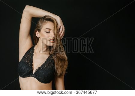 Portrait Of A Girl In A Black Bra On A Black Background Raising Her Hand Above Her Head