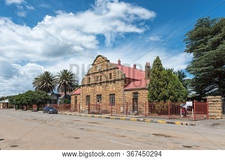 Clocolan, South Africa - March 20, 2020: A Street Scene, With The Historic Sandstone Town Hall, In C
