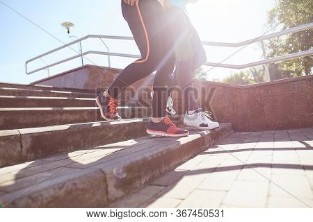 Morning Workout. Cropped Photo Of A Couple In Sportswear Running Down The Stairs Outdoors. People In