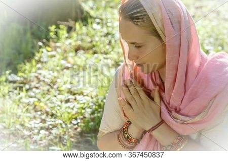 Calm Middle-aged Woman In Pink Shawl Praying In Green Park