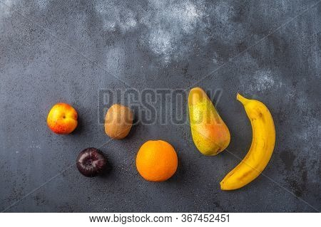 Ingredients For Fruit Salad On A Dark Wooden Surface. Top View. Copy Space