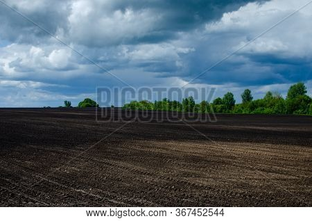 Dark Rainy Clouds Above Plowed Field. Plowed Field And Forest Nearby. Agriculture