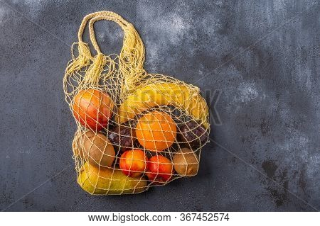 Fruits In The Range In Yellow Eco String Bag On A Dark Wooden Surface. Environmental Protection Conc