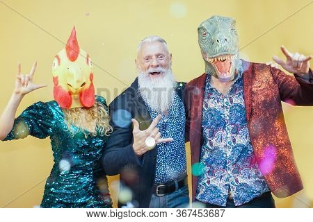 People Dancing At Carnival Party Wearing T-rex And Chicken Mask. Friends Having Fun Listening Rock M