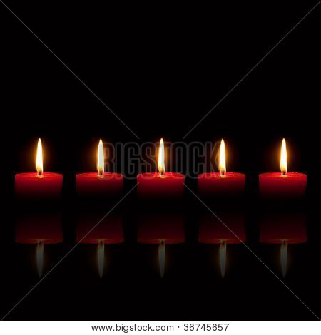 Five Red Candles Burning In Front Of Black Background