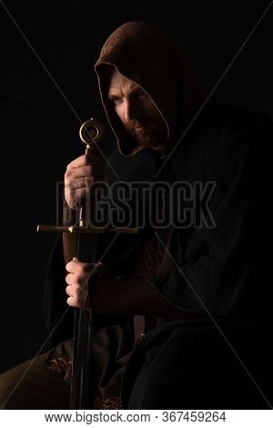 Tense Medieval Scottish Man In Mantel With Sword In Dark Isolated On Black