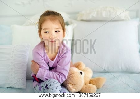 Portrait Of Small 3 Years Old Sulking Capricious Girl Sitting In Bed In Pajama With Her Toy Bear. Em