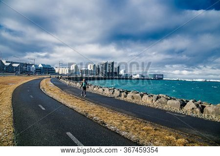 Reykjavic , Iceland- Feb 20, 2020:  Woman walk at  promenade along sea on cloudy sky in Reykjavik, Iceland. Promenade at seaside on cityscape. Travel and wanderlust on urban landscape. Iceland.