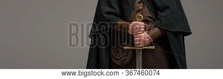 Cropped View Of Medieval Scottish Knight In Mantel With Sword In Hands On Grey Background, Panoramic