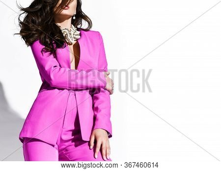 Young Beautiful Brunette Business Woman In Bright Purple Suit And Massive Necklace Standing And Hold