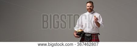 Smiling Scottish Redhead Man In Red Kilt Holding Potty With Gold Coins On Grey Background, Panoramic