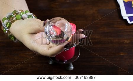 New York, Usa-19.05.2020: A Fortune Teller Holds A Magic Ball.on The Table Are Fortune-telling Cards