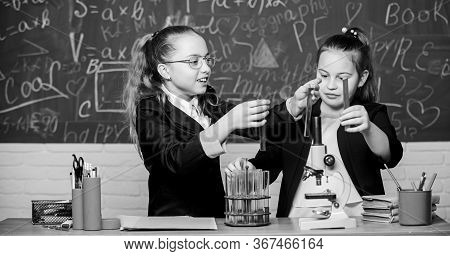 Educational Experiment Concept. Girls Classmates Study Chemistry. Microscope And Test Tubes On Table