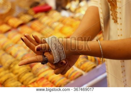 Hands Of A Woman Trying To Wear Of Bangles On Her Hand.selective Focus With Copy Space For Text.