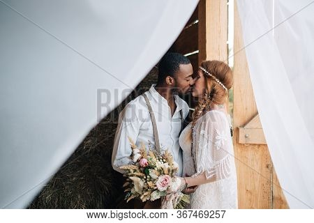 Newlyweds In The Style Of Boho. African Groom Hugs A Caucasian Bride In A Barn.