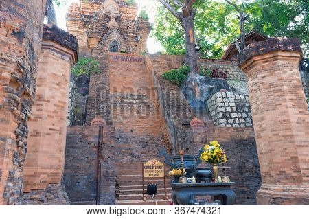 Altar With Offerings And Flowers And A Tall Staircase To Red Brick Monument On Cham Tower Monument