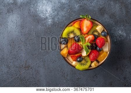 Fresh Fruit Salad With Different Ingredients On Dark Background. Healthy Diet. Copy Space For Text.