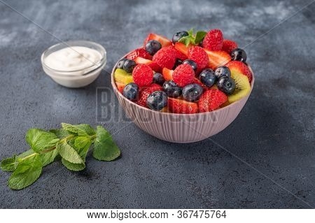Fresh Fruit Salad With Different Ingredients With Mint And Sour Cream On Dark Background. Healthy Di
