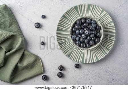 Blueberries Into Bowl On A Plate With Napkin On A Light Wooden Background. Top View. Copy Space For