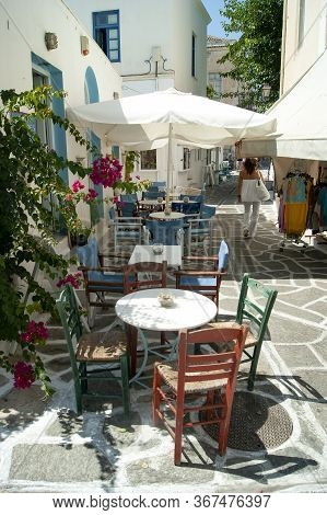 A Pretty, Shaded Alley At The Old Town At The Port Of The Greek Island Of Paros. A Cafe With Traditi