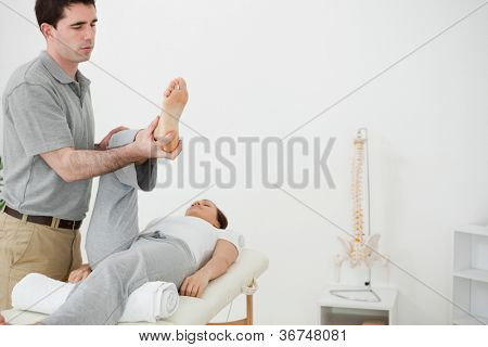 Brunette physiotherapist manipulating the leg of a woman in a room
