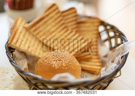 Round Bun And Fried Toasts. A Small Basket With Bread, Toasts And A Sesame Bun.