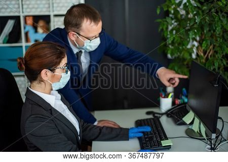 Colleagues In Surgical Masks In An Open Office Space Communicate At The Work Desk. A Male Top Manage